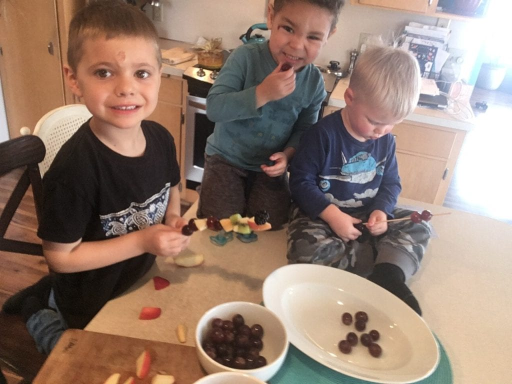 boys making fruit kabobs